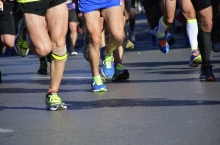 Marathon running race, people feet in sport shoes on road